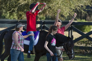 hippotherapy child on horse arms raised